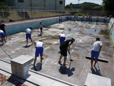 プール清掃をする生徒たち